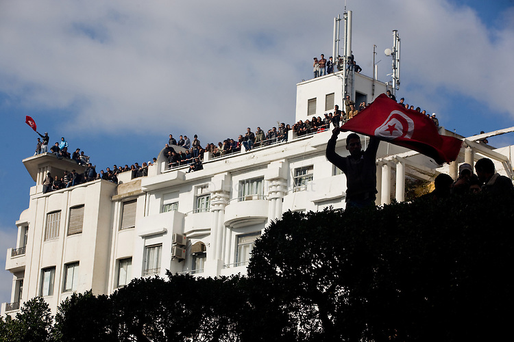 A man waved a Tunisian flag while people watched the  protest from above in downtown Tunis, Tunisia, Jan. 14, 2011. Several thousand people gathered outside the Ministry to protest and ask President Zine El Abidine Ben Ali to resign.