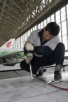 Workers repair Boeing aircrafts in the hangar of Aircraft Maintenance & Engineering Corporation (AMECO), Beijing, China..23 Jan 2005
