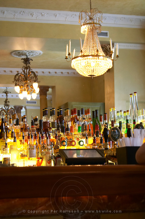 Bistro Jarl restaurant and wine bar. wine and spirits bottles on shelves. Crystal chandelier in the mirror. Stockholm. Sweden, Europe.