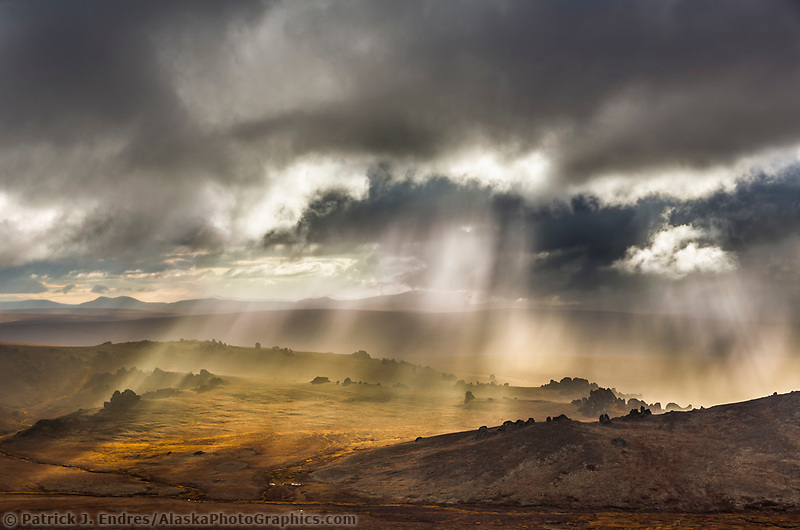 Sun streams through the clouds over the granite tors of the Bering Land Bridge National Preserve, Seward Peninsula, Alaska.