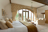 There is plenty of room in the spacious master bedroom for a seating area next to the large arched window
