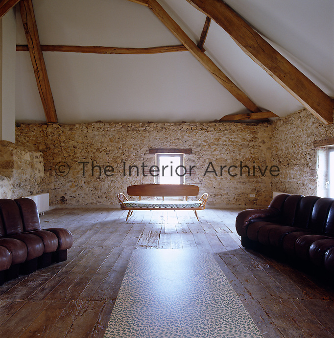 An Ercol daybed and and a snaking 10 metre Ueli Berger sofa furnish the converted granary
