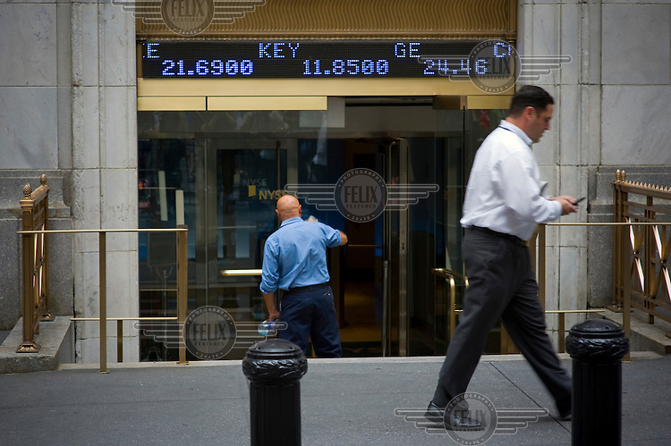 A Wall Street banker walks past the New York Stock Exchange (NYSE) on the day when share prices plummeted after the US Government failed to reach an agreement to bail out the country's ailing financial institutions.