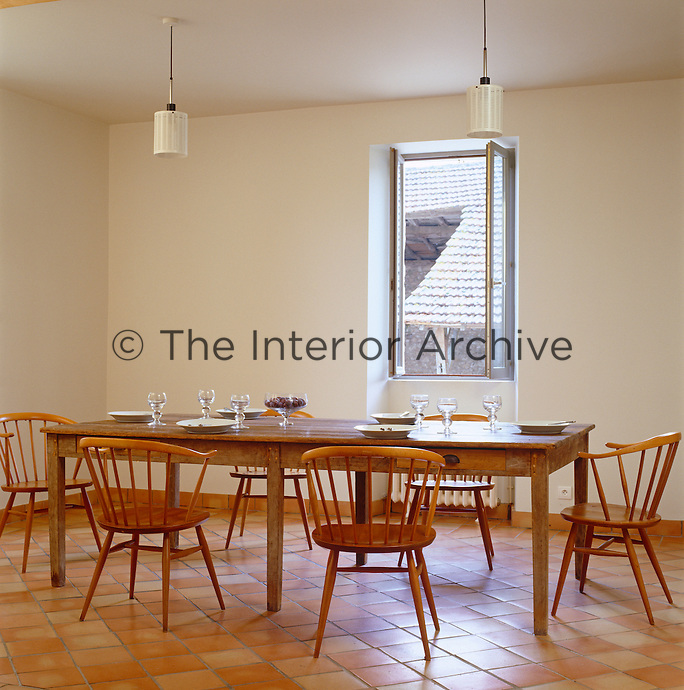 Ercol chairs surround a 1930s French post-office sorting table in the dining room