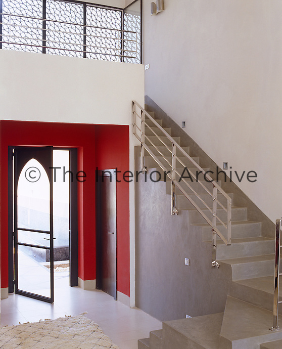 A modern and sleek entrance hall in a variety of finishes with an accent of red