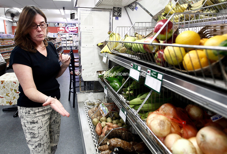 Waterbury, CT- 03 October 2013-100313CM01-  Kathleen Novak, with the city Health Department shows off fruits and vegetables inside D&M Superette in Waterbury Thursday afternoon.  The city Heath Department is putting forth an effort to bring fresh fruits and vegetables to local markets.   Christopher Massa Republican-American
