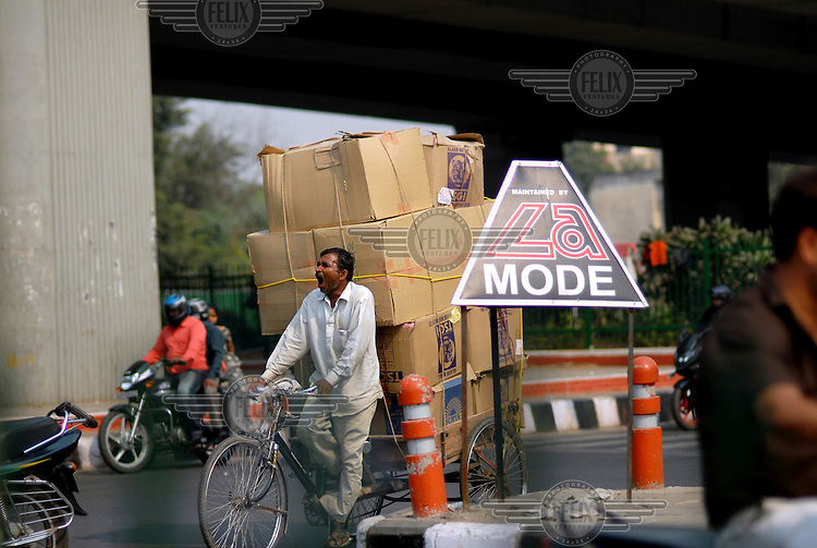 Yawning cyclist carrying bulky load on one of the ring roads of New Delhi.