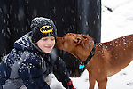 "Cute young dog ""kisses"" boy on the cheek in a snow storm"