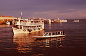 Manaus, Brazil. Cortez Filho 'Gaiola' riverboat and a smaller boat at dusk. Amazonas State.