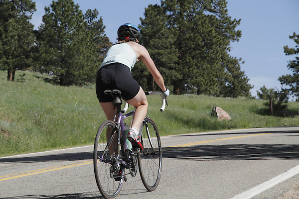 Caucasian female biking uphill on Lookout Mountain Road west of Denver, Colorado. .  John leads private photo tours in Boulder and throughout Colorado. Year-round.