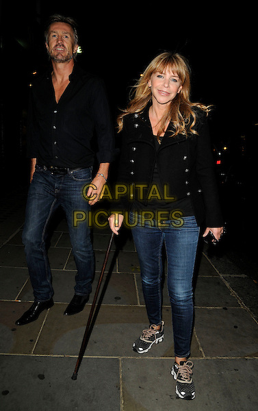 LEE CHAPMAN & LESLIE ASH.The Juju party, Juju bar & restaurant, King's Rd., London, England..September 3rd, 2009.full length black shirt jacket cane walking stick sneakers trainers married husband wife .CAP/CAN.©Can Nguyen/Capital Pictures.