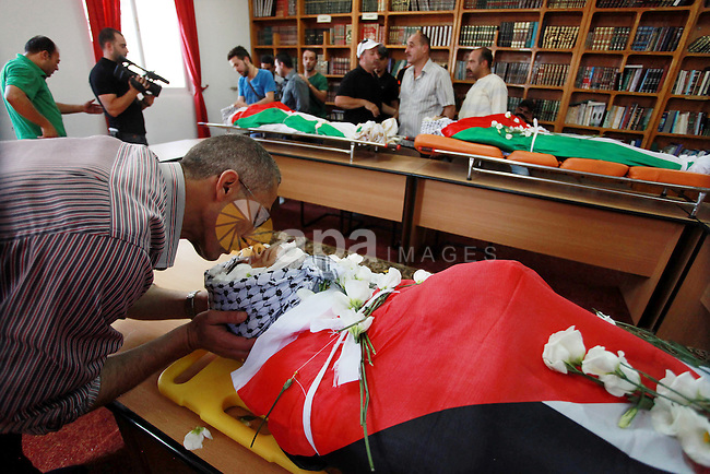 The bodies of Robin Zayed, Younis Jahjouh and Jihad Aslan lie in a mosque during their funeral at Qalandiya Refugee Camp near the West Bank city of Ramallah August 26, 2013. Israeli troops shot dead three Palestinians, including Jahjouh, and wounded about a dozen in an early morning raid on Monday to arrest a suspected militant in a refugee camp near Jerusalem, Palestinian medical sources told Reuters. An Israeli police spokesman said the clash erupted when border police carrying out an arrest raid were confronted by Palestinians who threw firebombs and rocks at them. Photo by Issam Rimawi