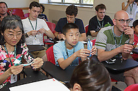 OrigamiUSA 2016 Convention at St. John's University, Queens, New York, USA. Creasers in Kade Chan's Capricorn class. Raymond Zhao (m), New Jersey, helps Robin Matsumoto (l), Toronto, Canada, and first timer Brian Hoffman (r), Vermont.