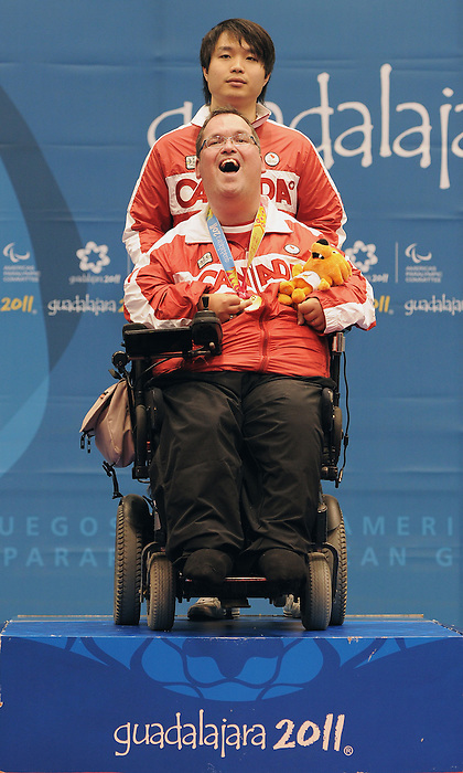 November 16 2011 - Guadalajara, Mexico:  Paul Gauthier is all smiles with his assistant Benson Au after winning the Gold Medal in Boccia BC2 in the Multipurpose Gymnasium Revolución at the 2011 Parapan American Games in Guadalajara, Mexico.  Photos: Matthew Murnaghan/Canadian Paralympic Committee