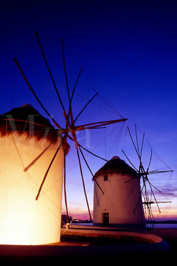 Greece. Mykonos Town. Illuminated windmills at dusk.