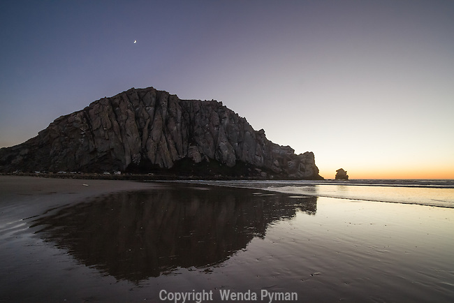 A crescent moon sets over Morro Rock at twilight, reflected in the wet sand.