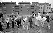 Passing an object between the legs game, Festival & Gala Day at the Education Centre, Wester Hailes, Scotland, 1979.  John Walmsley was Photographer in Residence at the Education Centre for three weeks in 1979.  The Education Centre was, at the time, Scotland's largest purpose built community High School open all day every day for all ages from primary to adults.  The town of Wester Hailes, a few miles to the south west of Edinburgh, was built in the early 1970s mostly of blocks of flats and high rises.