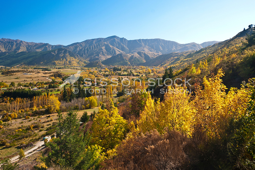 Autumn trees across Wakatipu Basin towards historic Arrowtown village. Seen from the Crown Range Road, Central Otago, South Island, New Zealand