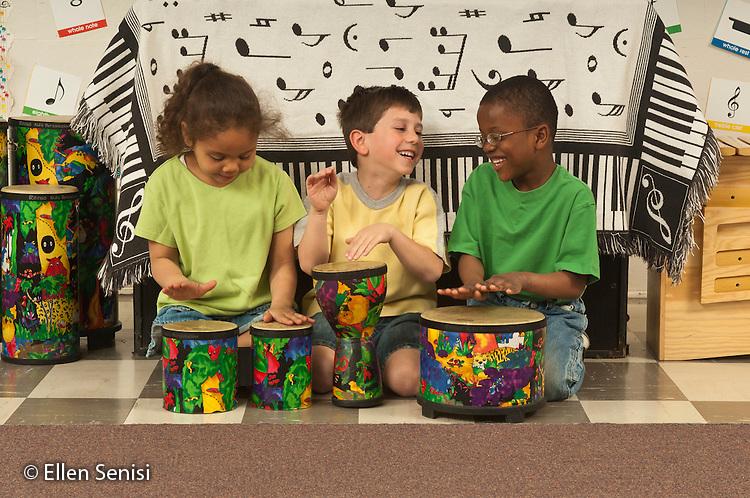 MR / Schenectady, New York. Elmer Avenue School (urban public elementary school). Kindergarten classroom. Students play hand drums together during music class. Left: girl, age 5, African-American / Caucasian; center: boy, age 5; right: boy, age 5, African-American. MR: Wil32, Bea9, Jos2. ID: AH-gKg. ©Ellen B. Senisi.