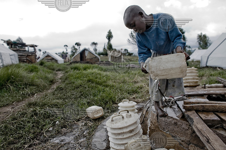 A child collects water from a well at a camp near Eldoret. A year after a political crisis led to violence, tens of thousands of those displaced still live in the IDP (Internally Displaced Persons) camps in the Rift Valley.