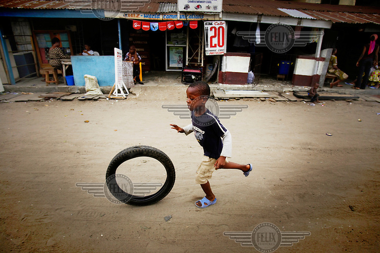 A boy plays with a tyre in the Ajegunle slum.