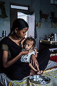 18 month old Prahlad Ramesh, an extremely malnourished boy is fed by his 21 year old mother, Rekha at the Nutrition Rehabilitation Centre (NRC) in Khaknar block of Burhanpur district in Madhya Pradesh, India. Prahlad was admitted to the NRC on Sept 13, 2012 and weighed 4.400Kg and his weight on Sept 18, 2012 was recorded at 4.730Kg. Photo: Sanjit Das/Panos for ACF