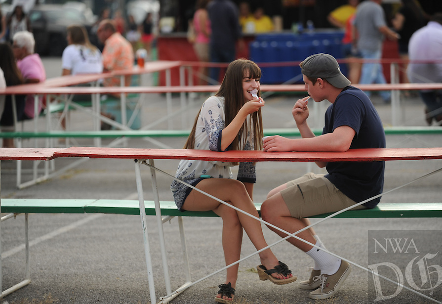 NWA Democrat-Gazette/ANDY SHUPE<br /> A couple eats Tuesday, Aug. 4, 2015, during the 117th annual Tontitown Grape Festival. The festival continues through Saturday. Visit nwadg.com/photos to see more photographs from the festival.