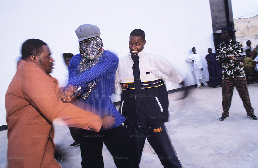 Husa youth street theatre perform how they are treated on the streets by state police, volunteer militias and vigilante groups..The implementation of Islamic Sharia Law across the twelve northern states of Nigeria, centres upon Kano, the largest Muslim Husa city, under the feudal, political and economic rule of the Emir of Kano. Islamic Sharia Law is enforced by official state apparatus including military and police, Islamic schools and education, plus various volunteer Militia groups supported financially and politically by the Emir and other business and political bodies. Fanatical Islamic Sharia religious traditions  are enforced by the Hispah Sharia police. Deliquancy is controlled by the Vigilantes volunteer Militia. Activities such as Animist Pagan Voodoo ceremonies, playing music, drinking and gambling, normally outlawed under Sharia law exist as many parts of the rural and urban areas are controlled by local Mafia, ghetto gangs and rural hunters. The fight for control is never ending between the Emir, government forces, the Mafia and independent militias and gangs. This is fueled by rising petrol costs, and that 70% of the population live below the poverty line. Kano, Kano State, Northern Nigeria, Africa