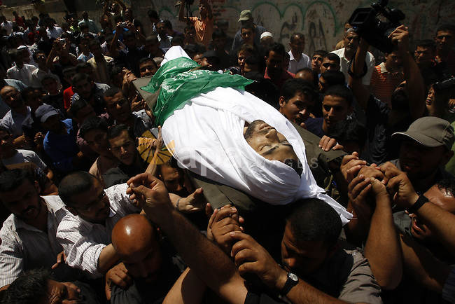 Palestinian mourners carry the body of Moussa Shtewi during his funeral in Gaza City on August 16, 2011 after he was killed and seven injured by overnight Israeli air strikes across the Gaza Strip, Palestinian medics said. The Israel Defence Forces (IDF) said the sites were targeted in response to the firing of a rocket from the Gaza Strip at the city of Beersheva. Photo by Mahmud Nassar