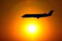 A plane is silhouetted against the setting sun as it makes its descent at Charlotte-Douglas International Airport in Charlotte, North Carolina. Charlotte-based photographer has other images of transportation, airplanes on runways (and taking off and landing) and interior/exterior airport images of Charlotte-Douglas Intl Airport in portfolio.