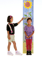 Young GIRLS use a sunflower designed measuring chart to determine their heights - model released.