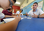 (09/18/17 Springfield MA)  Math teacher Evan Christensen works with seventh grade students during a math game on negative and positive numbers, in his class at John J. Duggan Academy, Monday, Sept. 18, 2017, in Springfield. The students are Josue Ruiz, foreground, Yasmine Badillo, center, and Tyshawn Heslope. Herald Photo by Jim Michaud