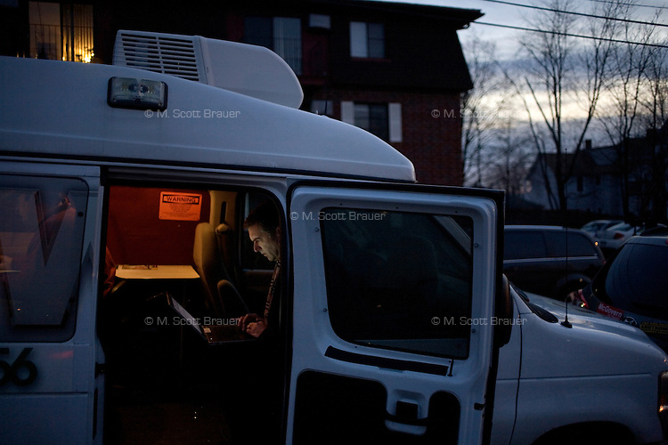 A reporter uses a laptop in a news van as former senator Rick Santorum speaks to a crowd made primarily of media and protestors outside Belmont Hall and Restaurant in Manchest, New Hampshire, on Jan. 6, 2012.  Santorum is seeking the 2012 GOP Republican presidential nomination.  Protestors were primarily from the Occupy New Hampshire group..
