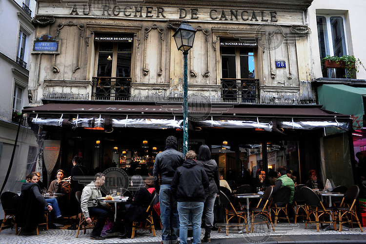 Some people wait outside while other dine at Au Rocher de Cancale restaurant in Paris..
