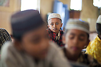 Children attend morning class at a mosque in Mawlamyaing in Mon state, Myanmar. The logo for the 969 sticker -  a movement that was started by Buddhist monks to encourage patrons to only shop at Buddhist owned businesses - was designed in Mawlamyaing.