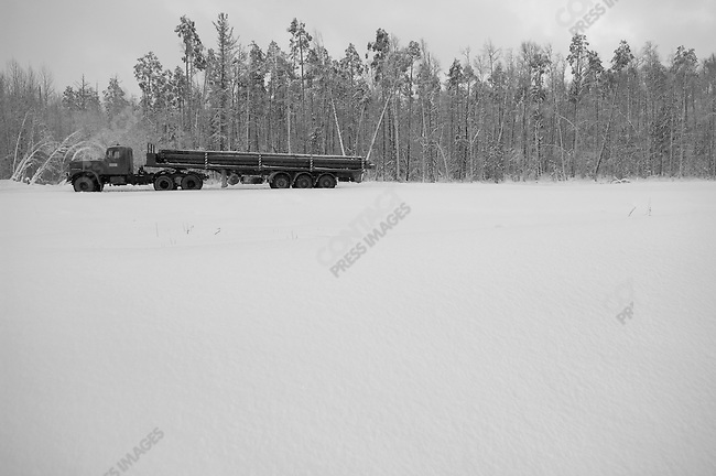 At a site in the vast Nefeyugansk oilfield in Siberia, Russia, the Siberian Geophysical Company, part of the oil services giant Schlumberger, are preparing wells for Rosneft, here a truck bringing new pipe for drilling waited to be unloaded. Siberia, Russia, November 20, 2007