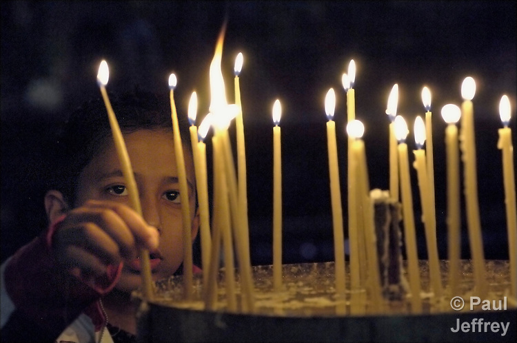 A boy lights candles in Bethlehem's Church of the Nativity, inside the occupied Palestinian West Bank.