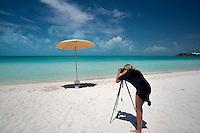 Photographer shooting umbrella Sappodilla Bay. P{rovidenciales, Turks and caicos