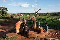 Children pumping water at the well. Kigulu town, Klobulenzi, Uganda, Africa