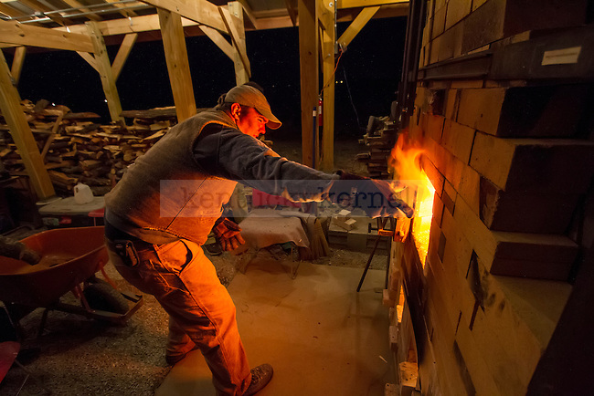 Professor Hunter Stamps carefully tosses a log into the kiln as fire rushes out to bite the hand that feeds it. The kiln was monitored, stoked, and fed logs 24 hours a day for 3 days straight in order to reach temperatures in excess of 2100°F. in Lexington, Ky., on Saturday, November, 17, 2012. Photo by James Holt | Staff