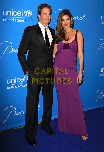 RANDE GERBER & CINDY CRAWFORD .UNICEF Ball held At The Beverly Regent Hotel, Beverly Hills, California, USA, .10th December 2009..full length purple dress long maxi sequined sequin sleeveless couple husband wife black suit tie .CAP/ADM/KB.©Kevan Brooks/AdMedia/Capital Pictures.