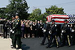 Thousands of police officers and military turned out for the funeral of James McNaughton, the first NYPD officer killed in the war in Iraq. James McNaughton's casket is carried into St. Elizabeth Ann Seton Church. His family stands behind. (From right to left front row)<br />
