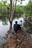 A man fishes in a mangrove forest in northern Jakarta.<br /> <br /> To license this image, please contact the National Geographic Creative Collection:<br /> <br /> Image ID: 1588074 <br />  <br /> Email: natgeocreative@ngs.org<br /> <br /> Telephone: 202 857 7537 / Toll Free 800 434 2244<br /> <br /> National Geographic Creative<br /> 1145 17th St NW, Washington DC 20036