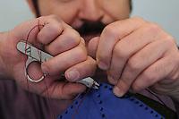 Claudio Sanò, artigiano del cuoio nel suo laboratorio mentre lavora un borsa a forma di pesce.<br /> Claudio Sanò, leather craftsman in his workshop, while he working a bag like a form of  big fish