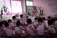 "MAE CHEE TIAP teachs ""Dharma songs"" to the children in a Public Kindergarden where she works as professor after had collected charity in the neighborhood streets. She has been professor during 2 years and ordained as a nun since 2 months, but served as volunteer during several years at the Sathira Dhammasathan centre. Dressed in white-clad, she keeps the eight precepts and has her head and eyebrows shaved when she teachs at the Kindergarden, where children learn to pray and offer salutations to Buddha every morning."