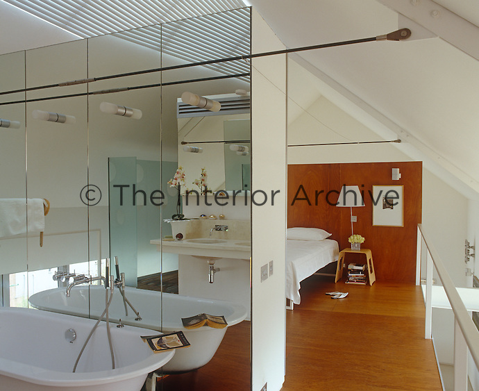 A partition separates the master bedroom from the bathroom which is lit by lights emerging from a mirrored wall