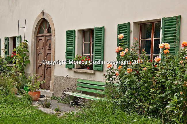 House with green window shudders and roses in Bondo, a Bregaglia Swiss Valley town, where the houses date back to the 16th century; Graubunden Canton in Switzerland