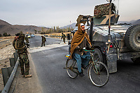 DASH-E TOWP, WARDAK PROVINCE, AFGHANISTAN - NOVEMBER 4, 2013: An Afghan man cycles past, the Explosive Ordnance Disposal (EOD) team soldiers  of the 6th Kandhak, 4th Brigade of the 203rd corp perform their daily morning sweep for mines along Highway 1 between Sayadabad and Maidan Shahr on November 4, 2013 near Dash-E Towp, Wardak Province, Afghanistan. The EOD team used their hands and also hooks to search for command and remote-detonated mines along Highway 1.                    Photo by Daniel Berehulak for the New York Times