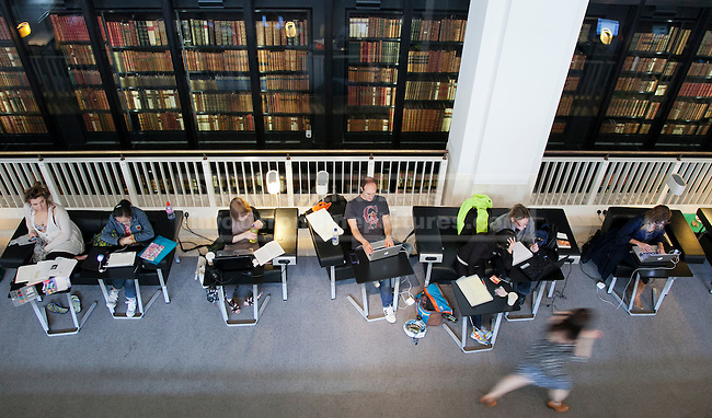 Stock images of people reading and working inside the British Library.