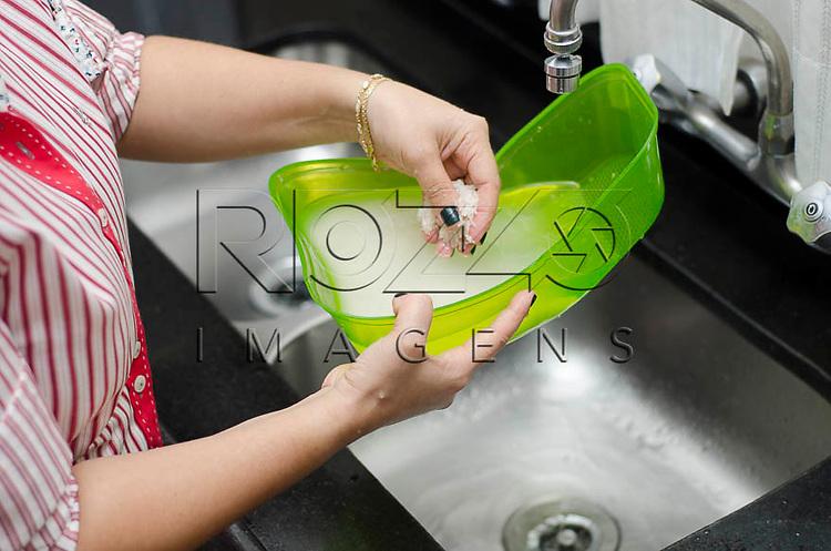 Mulher lavando arroz no escorredor, São Paulo - SP, 05/2014.